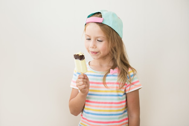 Menina comendo sorvete doce no palito