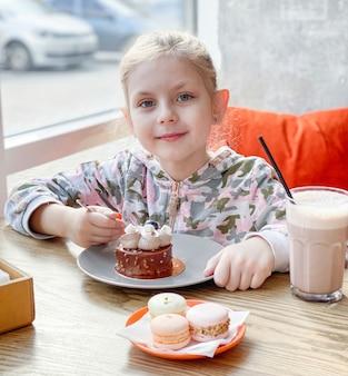 Menina comendo um bolo em um café
