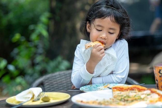 Menina comendo um pedaço de pizza ao ar livre