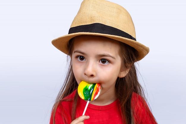 Menina comendo um pirulito.