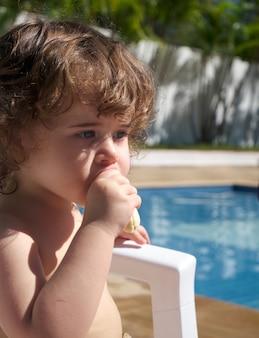 Menina comendo uma banana na piscina em um dia ensolarado.
