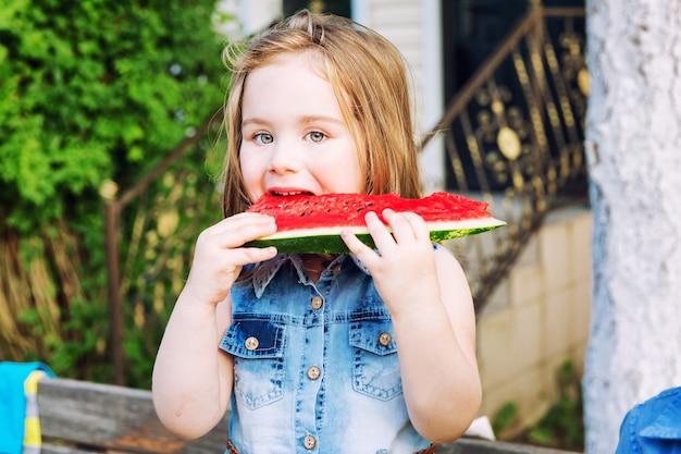 Menina comendo uma melancia no jardim