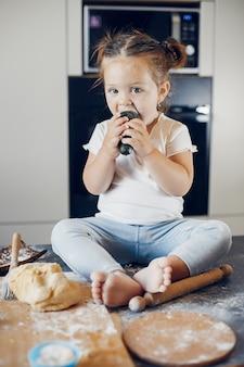 Menina comendo vegetais em uma mesa coberta com farinha
