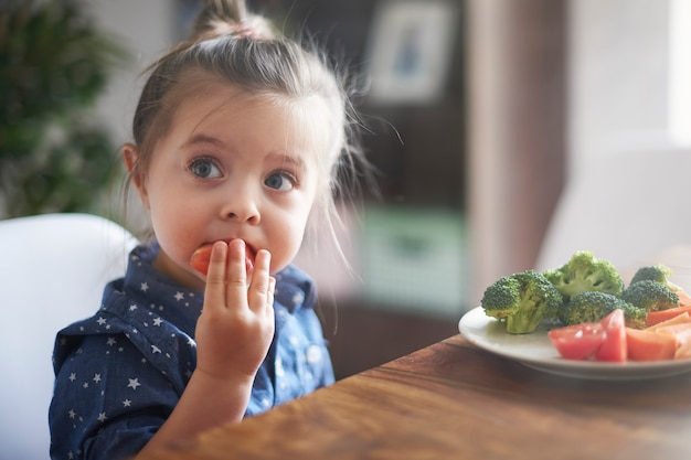 Menina comendo vegetais