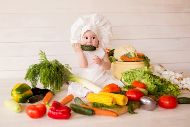Menina comer saudável de avental e chapéu prepara uma salada de legumes. cozinhar