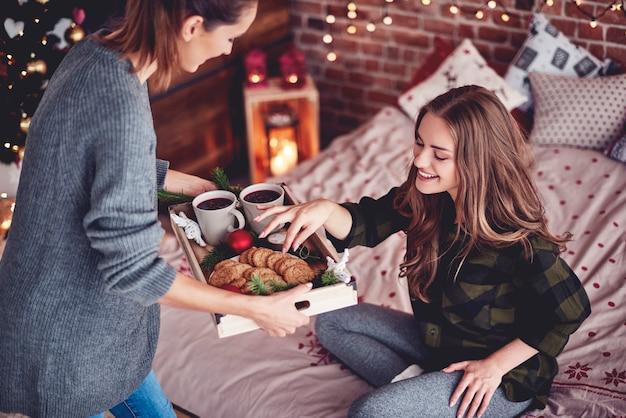 Menina compartilhando biscoitos e vinho quente com a amiga Foto gratuita