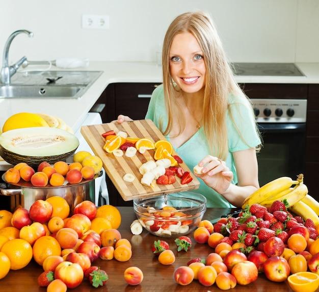 Menina comum de cabelos compridos que cozinha salada de frutas