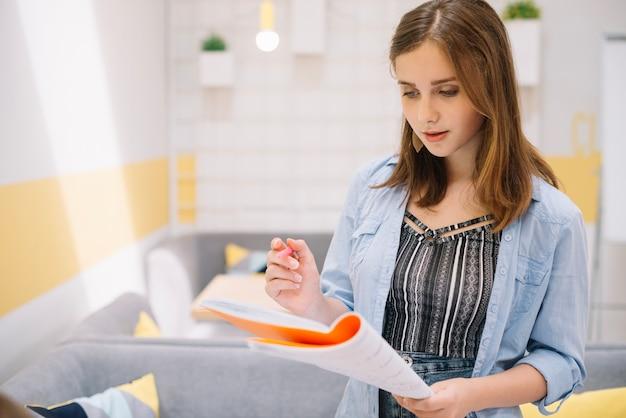 Menina concentrada posando com livro didático