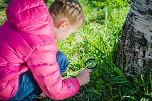 Menina concentrada usando uma lupa
