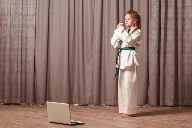 Menina conduzindo treinamento doméstico de caratê na frente de um laptop