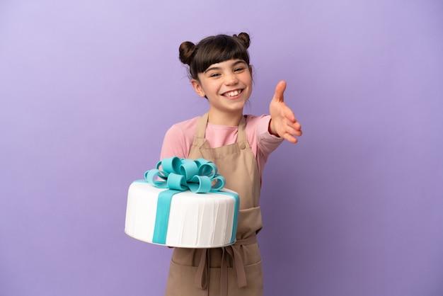 Menina confeiteira segurando um grande bolo isolado na parede roxa apertando as mãos para fechar um bom negócio