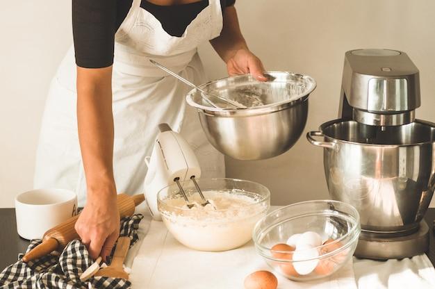 Menina confeiteiro está preparando um bolo