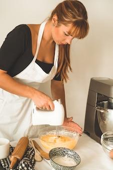 Menina confeiteiro preparando um bolo