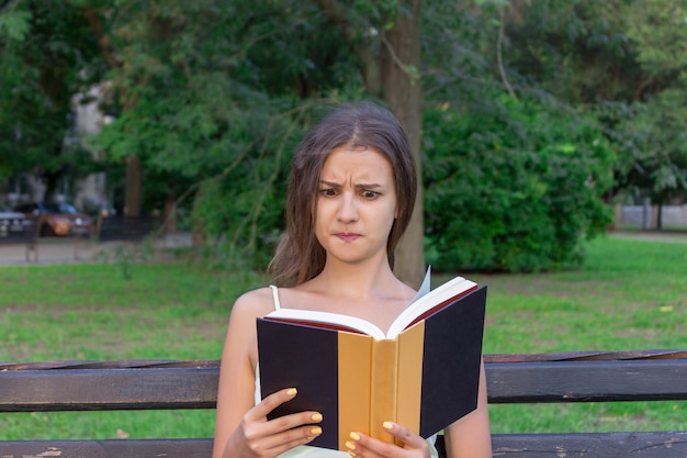 Menina confusa e descontente está lendo um livro no banco no parque