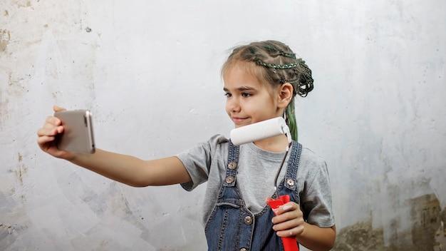 Menina consertando a sala, pintando a parede com a cor branca e fazendo selfie no smartphone