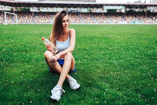 Menina consideravelmente desportiva que relaxa na grama após o treinamento
