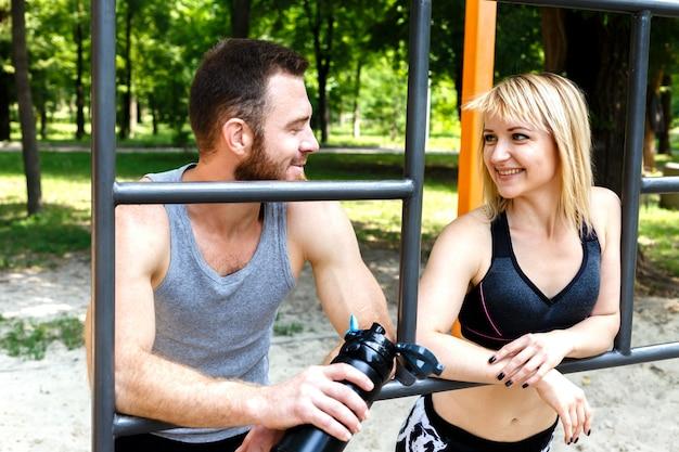 Menina consideravelmente loura e homem farpado que descansam após o treinamento do exercício em um parque ao ar livre.