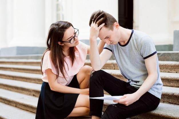 Menina consolando seu amigo frustrado deprimido e dá-lhe alguma ajuda