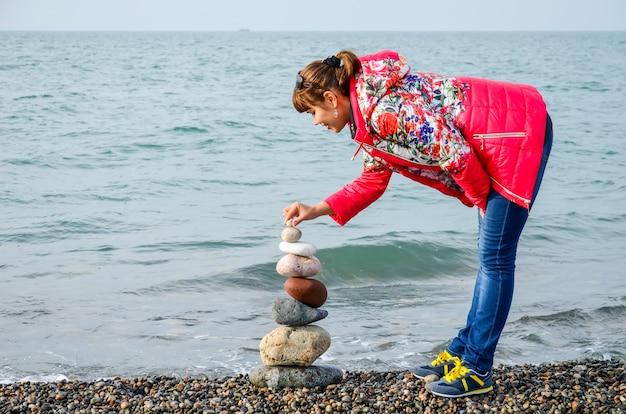 Menina constrói uma pirâmide de pedras coloridas no mar negro em batumi, geórgia.