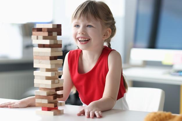 Menina construindo uma torre de blocos de madeira, jogos de tabuleiro com conceito infantil