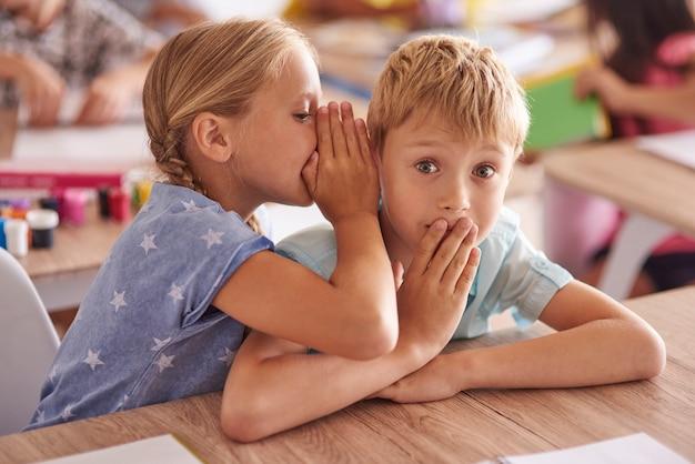 Menina contando um grande segredo para um amigo
