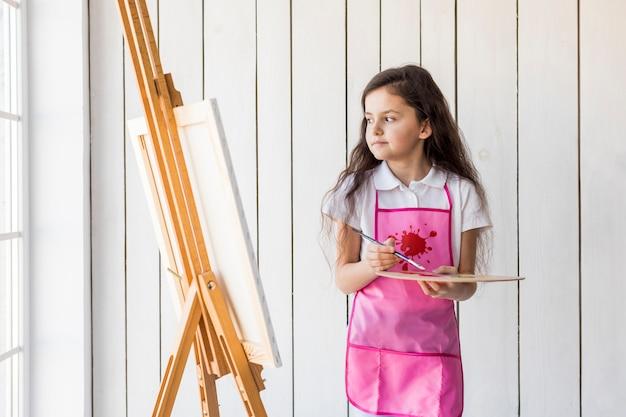 Menina contemplada com avental rosa segurando pincel e paleta