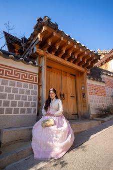 Menina coreana com hanbok, mulheres asiáticas retrato vestindo hanbok nas casas de estilo tradicional da aldeia de bukchon hanok em seul.