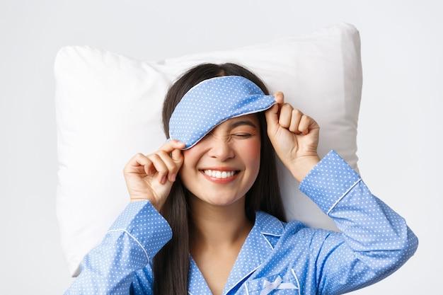 Menina coreana feliz e sorridente de pijama azul e máscara de dormir