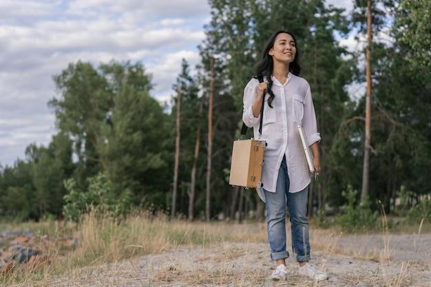 Menina coreana segurando a tela, pincel, apreciando a bela paisagem, procurando inspiração