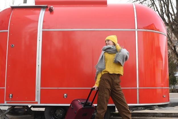 Menina corre com uma mala vermelha. van vintage retrô grande. carro velho viajando no inverno. garota com um chapéu amarelo brilhante e uma camisola de malha. conceito de viagem. copie o espaço