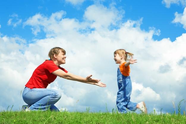 Menina corre para a mãe se abraçar na grama verde sob o céu com nuvens