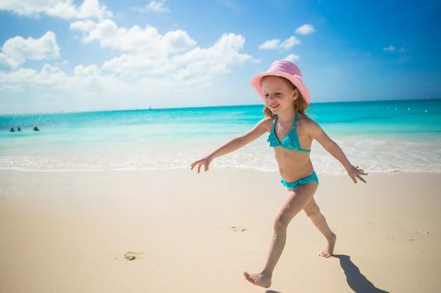 Menina correndo ao longo da praia e aproveite as férias de verão