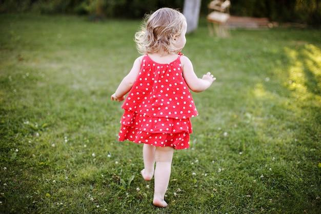 Menina correndo ao pôr do sol na grama