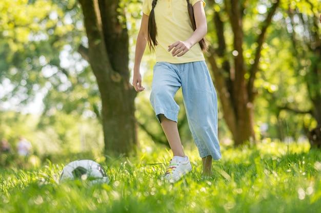 Menina correndo atrás da bola na grama