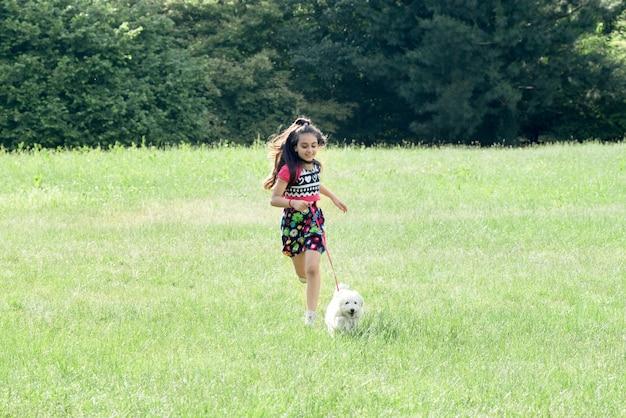 Menina correndo com seu poodle de estimação em um campo