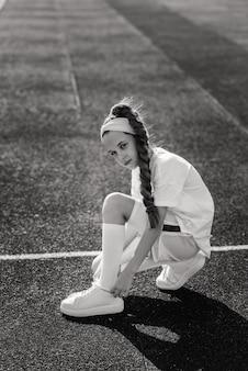 Menina correndo em uma noite ensolarada de verão, deitada na esteira, estádio, treinamento físico, volta às aulas, cansada.