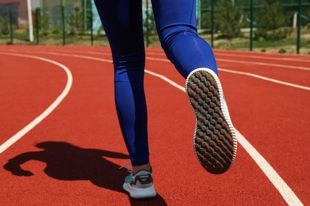 Menina correndo na pista atlética vermelha. conceito de esporte