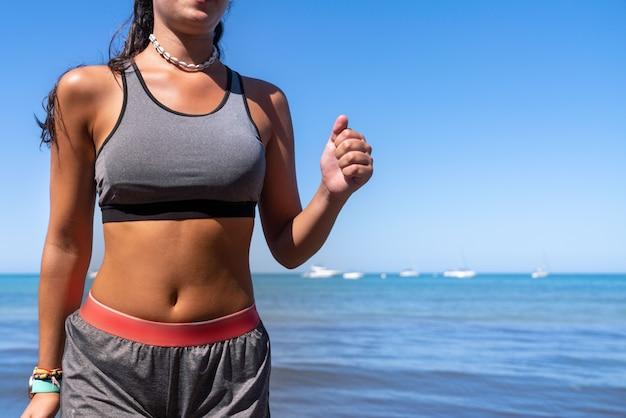 Menina correndo na praia com top, shorts e smartwatch