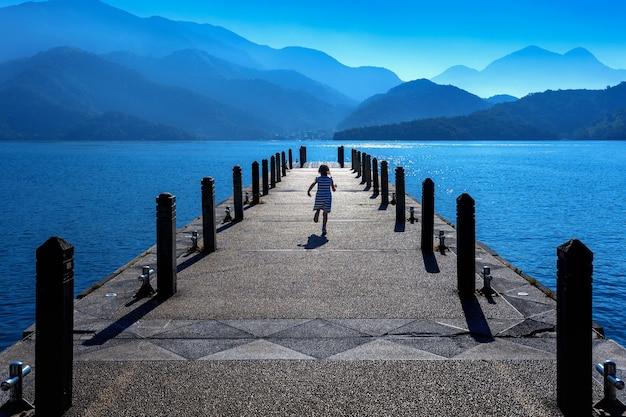 Menina correndo no caminho no lago sun moon, taiwan.