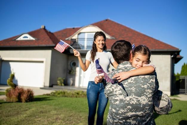 Menina correndo para o soldado do pai voltando da guerra e sua linda esposa agitando bandeiras