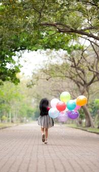 Menina correndo pulando e segurando um monte de um balões coloridos em sua mão.