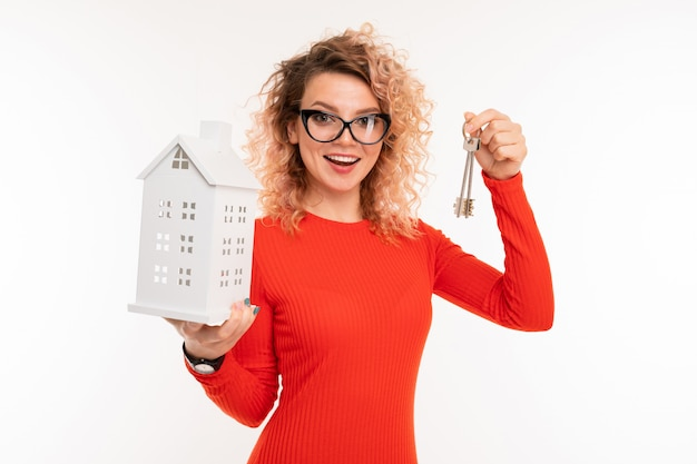 Menina corretor de imóveis detém as chaves e uma casa simulada em branco