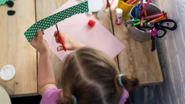 Menina corta entusiasticamente papelão colorido com tesoura, vista superior