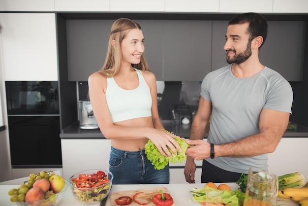 Menina corta legumes para uma salada e um homem a ajuda