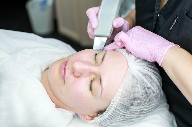 Menina cosmetologista fazendo limpeza ultrassônica do rosto