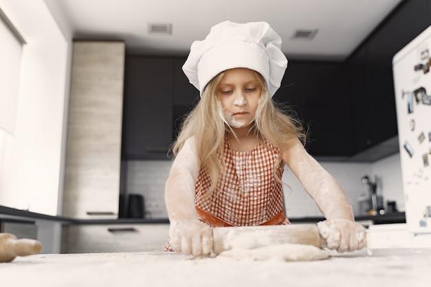 Menina cozinha a massa para biscoitos