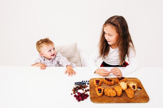 Menina cozinhando massa com o irmão, espaço livre na mesa da cozinha branca.