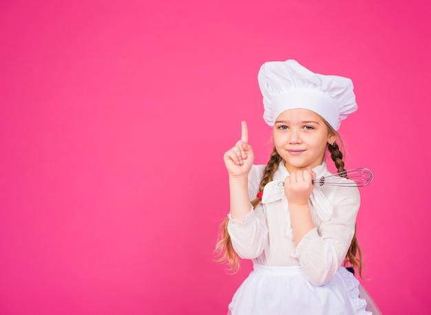 Menina cozinhar com batedor mostrando o dedo indicador