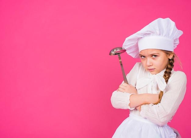 Menina cozinhar com concha travessia de braços