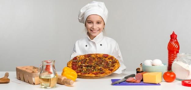 Menina-cozinhar com pizza nas mãos
